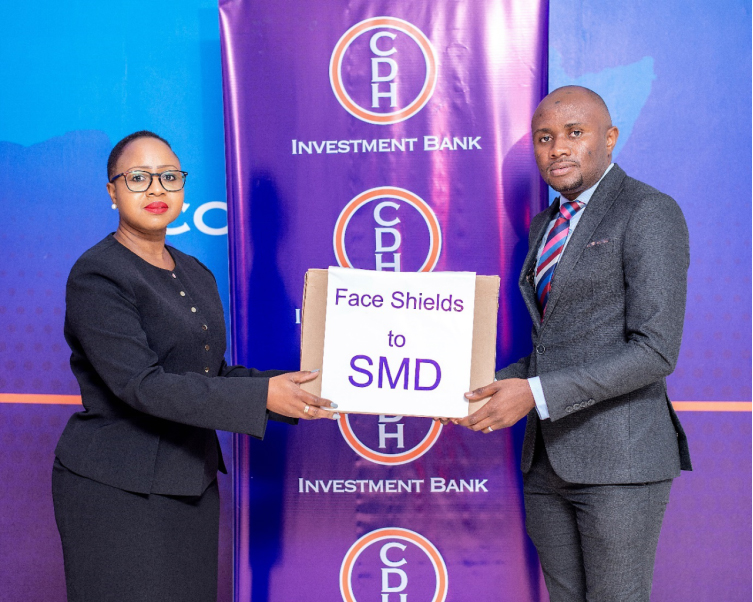 Mrs Beatrix Mosiwa-Ndovi, Chief Finance Officer of CDH Investment Bank hands over a box containing face shields to Dr Yamikani Moyo